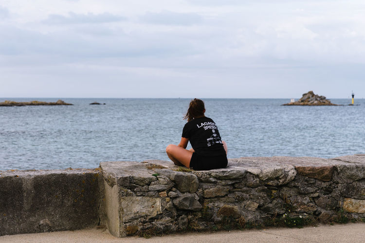 Young woman sitting at promenade of Roscoff Water Sky Sea Real People Lifestyles Leisure Activity Nature Scenics - Nature Beauty In Nature Day Horizon Horizon Over Water Outdoors Waterfront Roscoff Promenade Solitude Relaxing Depression Depression - Sadness One Person Sitting Rear View Looking At View