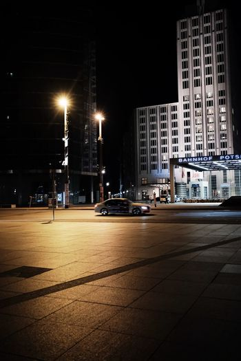 Cars on road by buildings against sky in city at night