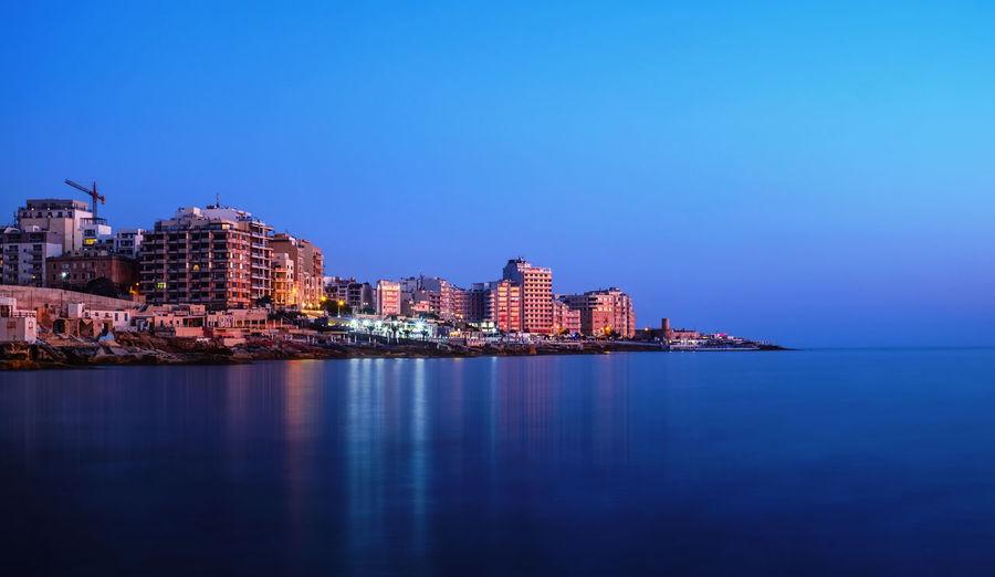 Illuminated buildings by sea against clear sky at dusk