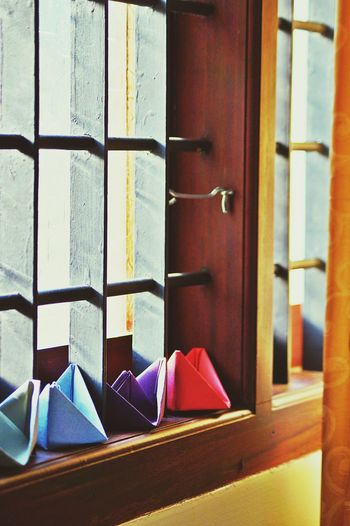 Close-up of colorful paper boats on window sill