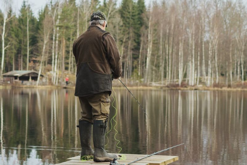 Full length rear view of man fishing by river against trees