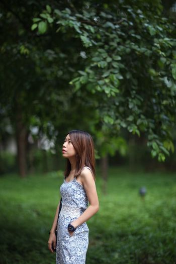 Side View Of Young Woman Standing By Trees On Field
