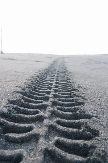 Tire tracks on beach against clear sky