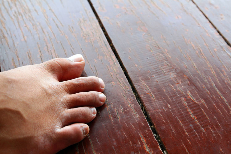 High angle view of person hand on wooden plank