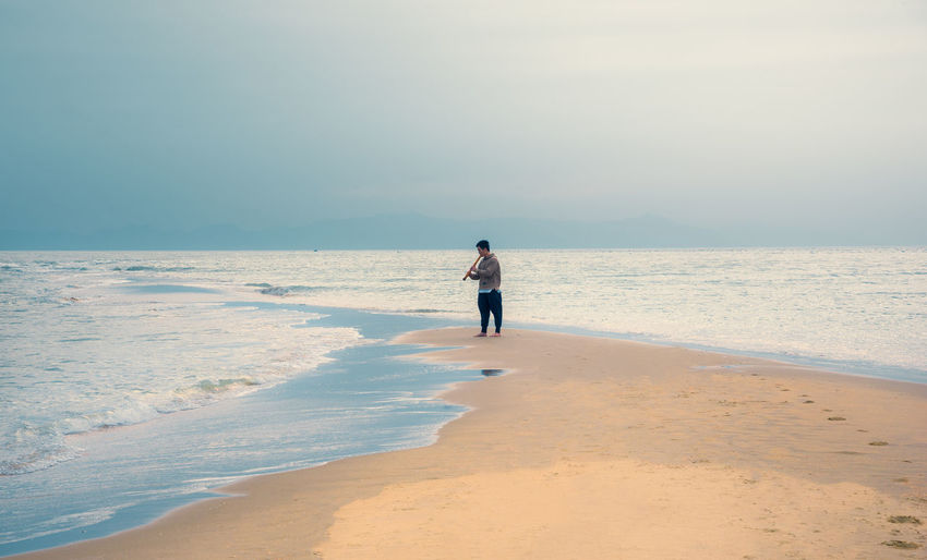 Man playing flute while standing at beach against sky