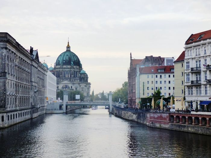 View Of Canal By City Against Sky