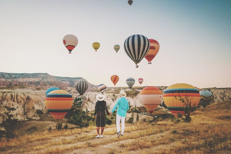 Rear view of couple looking at hot air balloons flying over land against sky