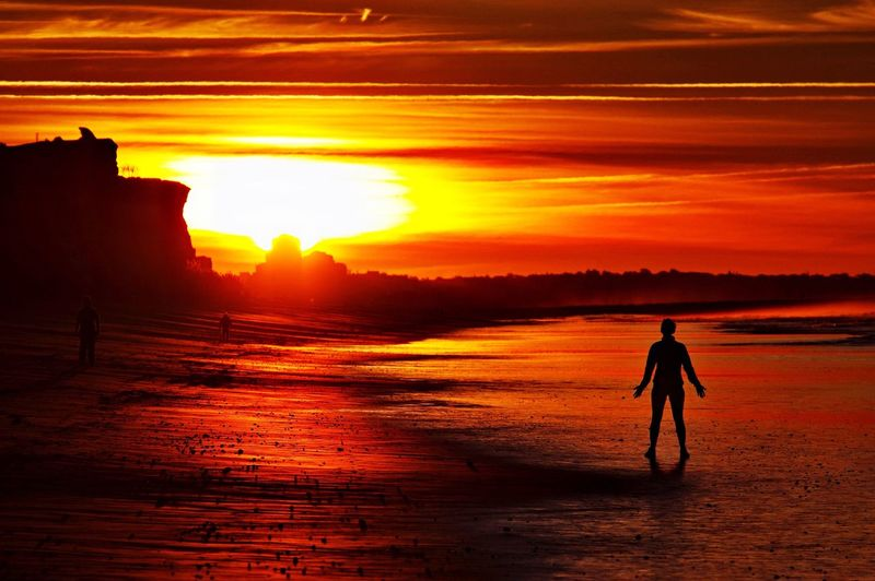 Silhouette Man On Beach Against Orange Sky During Sunset
