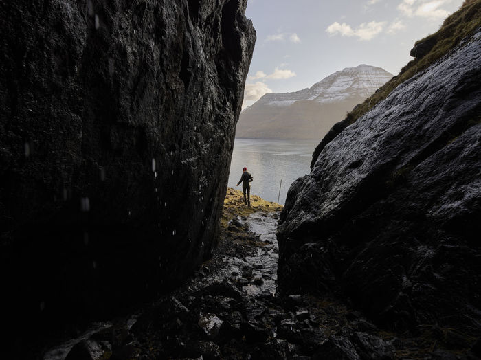 Man standing on rock by mountain against sky