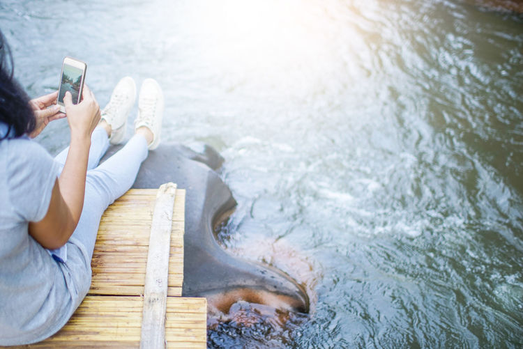 High angle view of woman sitting on pier at lake