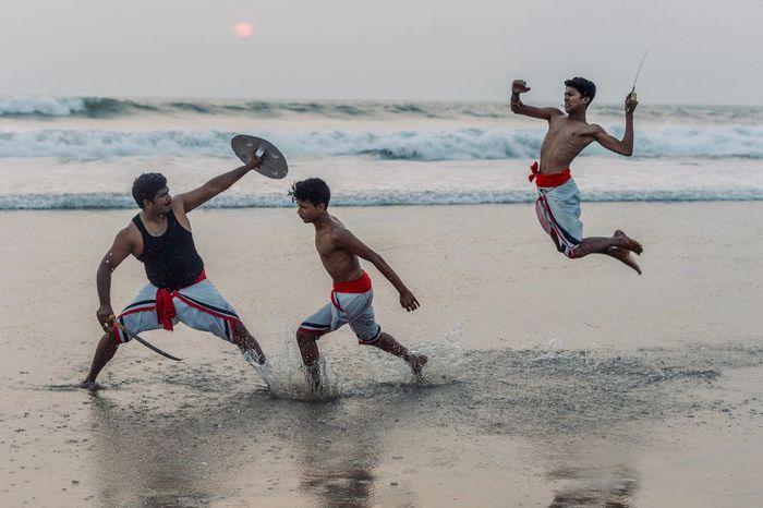FULL LENGTH OF MEN RUNNING ON BEACH