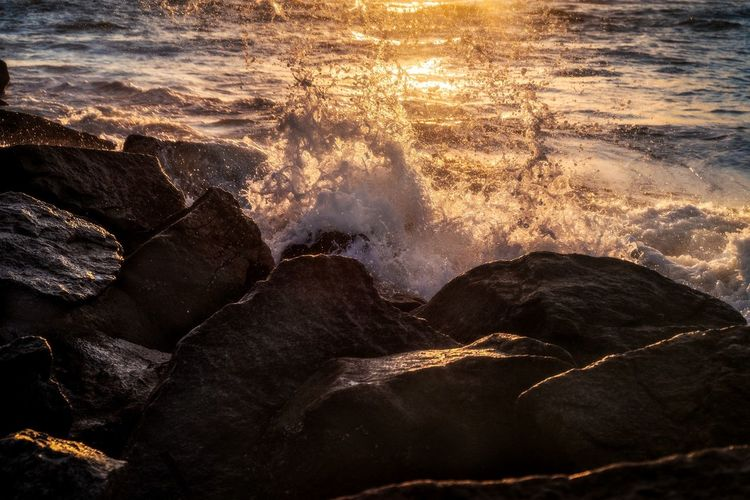 Waves splashing on rocks at shore during sunset