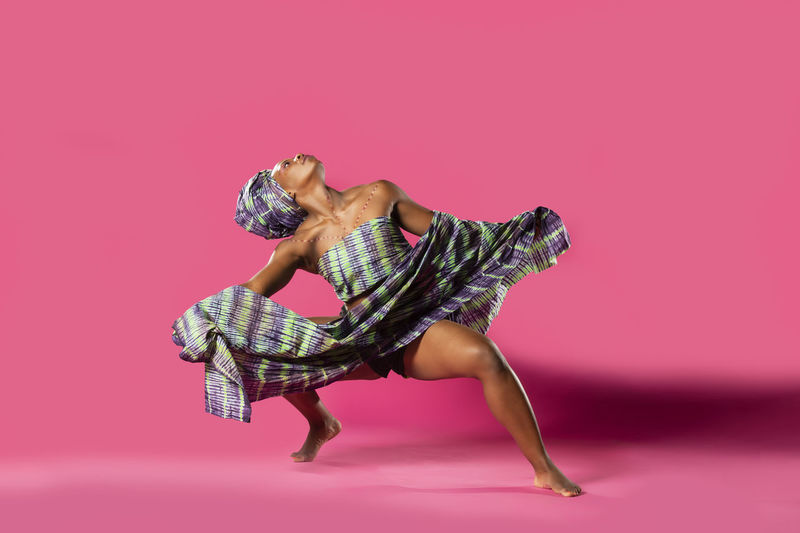 Woman in costume dancing against pink background