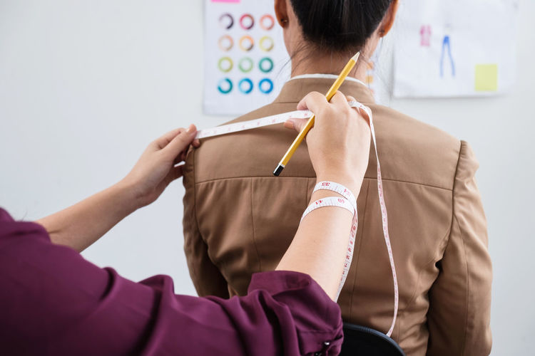 Cropped image of fashion designer measuring woman