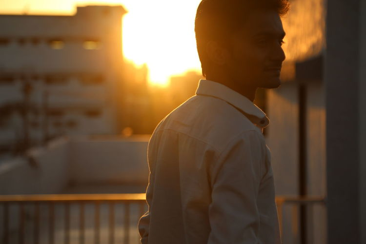 The Art Of Street Photography One Person Men Sunset Architecture Sunlight Standing Side View Built Structure Focus On Foreground Real People Lifestyles Males  Sky Waist Up Nature Building Exterior Outdoors Leisure Activity City Sun Lens Flare Profile View Exploring Fun My Best Photo The Minimalist - 2019 EyeEm Awards The Traveler - 2019 EyeEm Awards