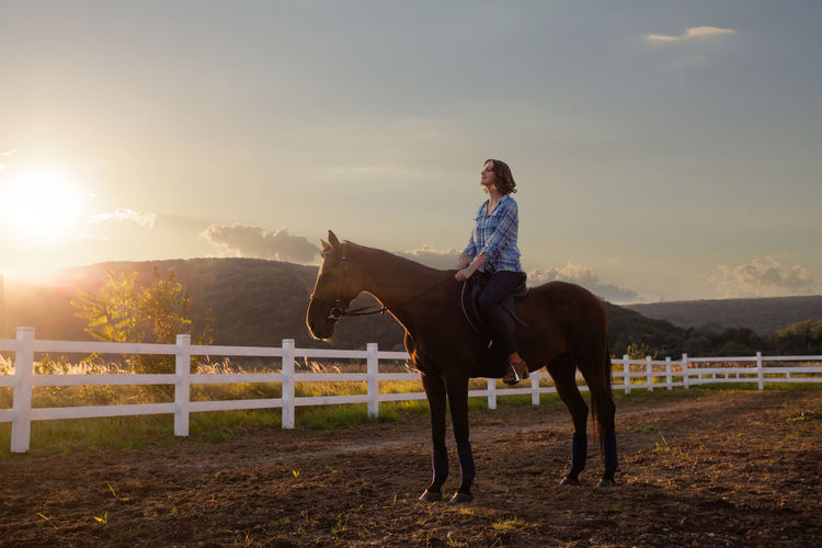 Full length of woman riding horse against sky