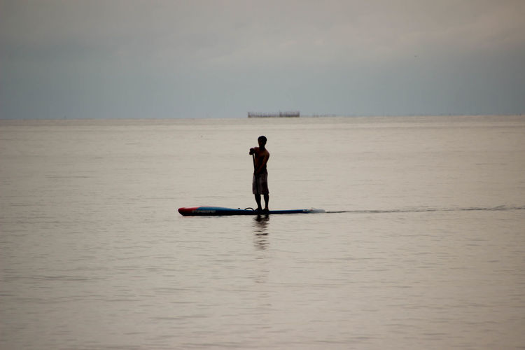 Silhouette man paddleboarding on sea during sunset