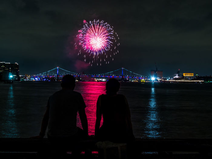 Two people in silhouette watching a firework display over the Delaware river and Ben Franklin Bridge in Philadelphia, PA. Ben Franklin Bridge Cityscape Explosion Fireworks Holiday Light Philadelphia Silhouette Arts Culture And Entertainment Bridge Celebration Colorful Event Exploding Firework Firework - Man Made Object Firework Display Fourth Of July Illuminated Independence Day Night Pyrotechnics River Two People Water
