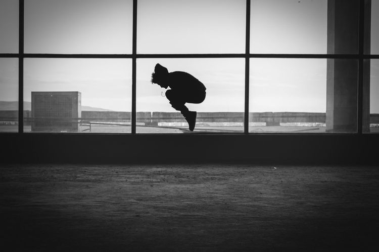 Silhouette Person Jumping In Building Against Sky
