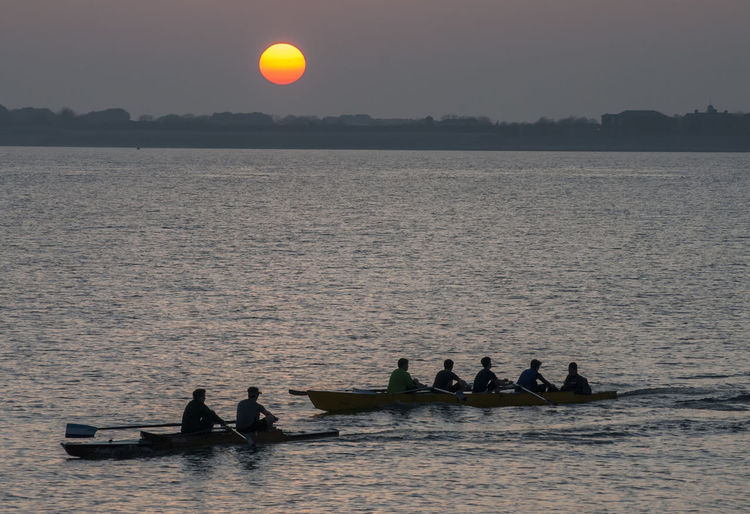 People Rowing On Sea During Sunset