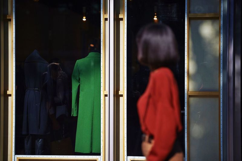 Side view of woman looking at window display