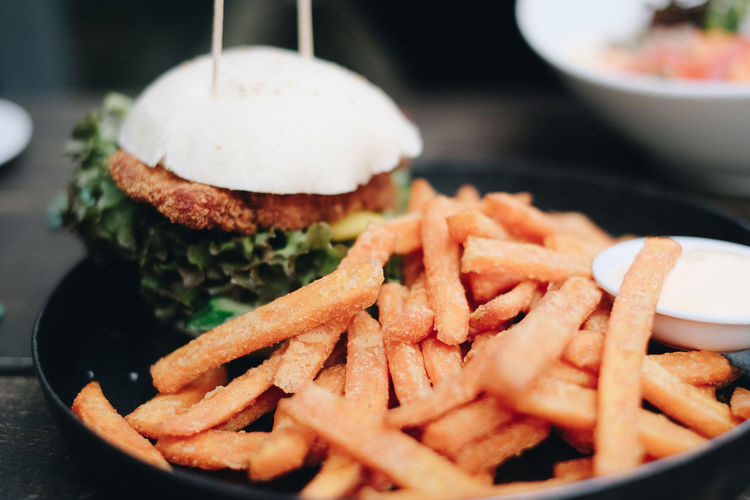 Close-up of burger and fries in plate on table