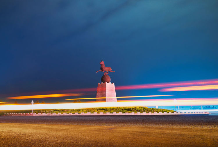 Monument Amidst Light Trails Against Blue Sky At Night