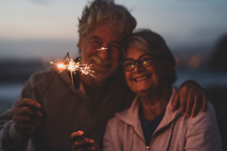 Smiling couple holding sparkler standing outdoors