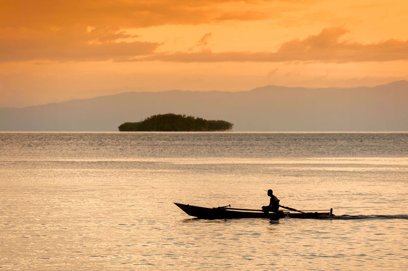 Raja Ampat, West Papua, Indonesia. A villager in Sapokren Village, South Waigeo, motors out for an evening of fishing during a glorious sunset. Adult ASIA Beauty In Nature Boat Canoe INDONESIA Island Kayak Man Motor Nature Nautical Vessel Ocean Outdoors Raja Ampat Remote Sea Silhouette Sky Southeast Asia Sunset Waigeo Waigeo Water West Papua