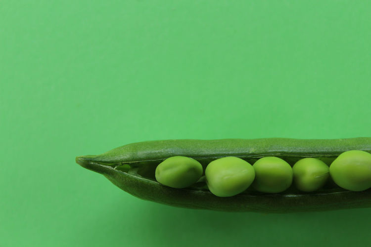 Close-up of green peas against green background