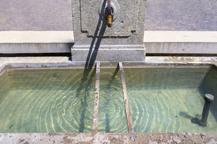 A natural source of water flowing from a copper tap in the wall to the tank, very clean water.
