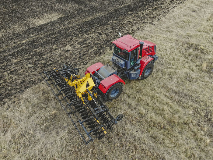 Aerial view of a modern tractor plowing dry field, preparing land for sowing Aerial Agriculture Field Tractor Farm Ground Soil Countryside Combine Machinery Motion Working Plowing High Angle View Transportation Agricultural Machinery Mode Of Transportation Rural Scene Outdoors Land Vehicle