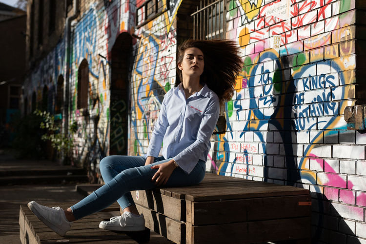 Portrait of confident young woman sitting on wood against graffiti wall in city