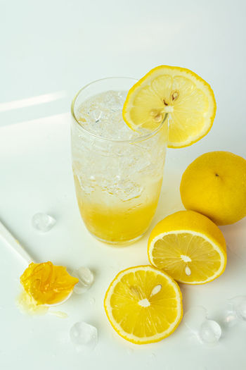 Yellow drink on table against white background