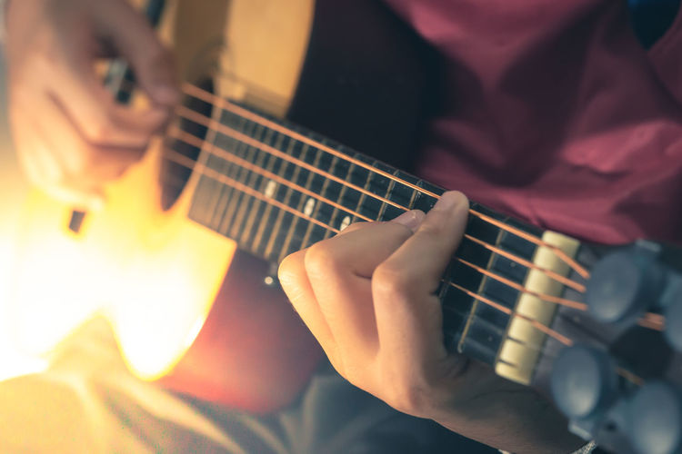 Midsection of man person playing guitar