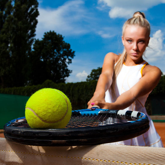 Tennis ball on the racket to the background of a beautiful woman. Close-up One Person Young Adult Sport Tennis Ball Tennis Ball Women Hair Young Women Blond Hair Waist Up Adult Day Sky Tennis Racket Leisure Activity Racket Front View Outdoors Beautiful Woman Hairstyle