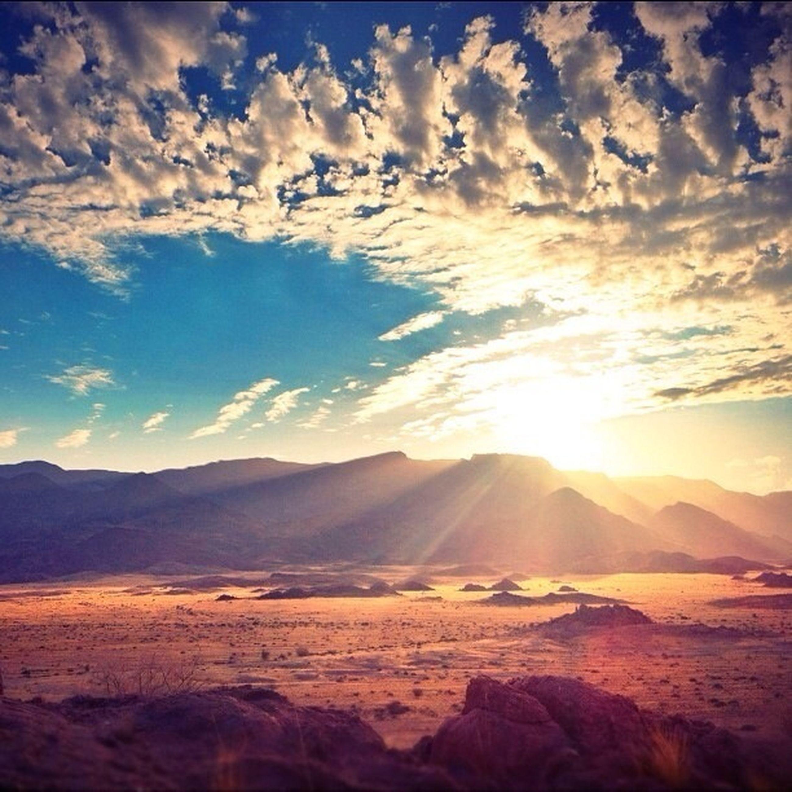 tranquil scene, tranquility, mountain, scenics, landscape, sky, beauty in nature, mountain range, nature, sun, sunlight, cloud - sky, sunbeam, sunset, non-urban scene, cloud, idyllic, remote, physical geography, desert