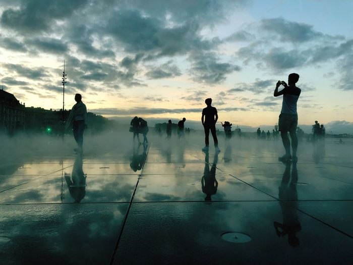 People on floor against sky during sunset