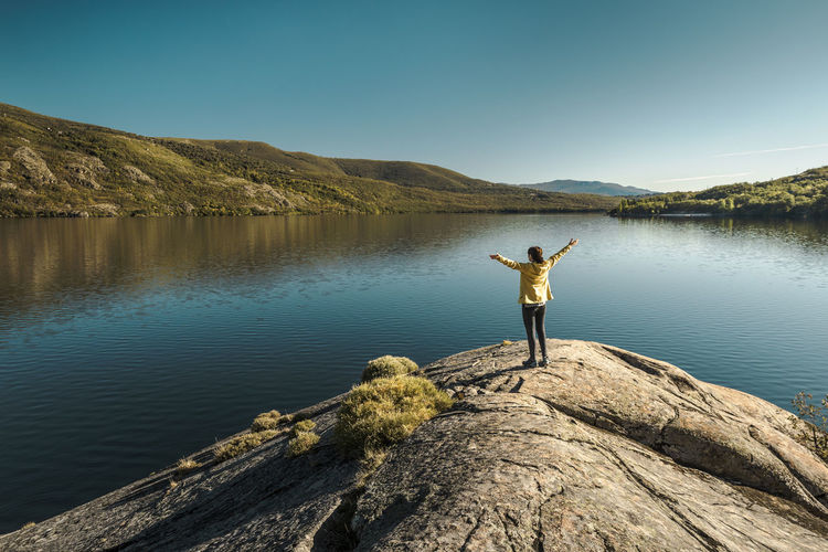 Man standing on rock by lake against sky