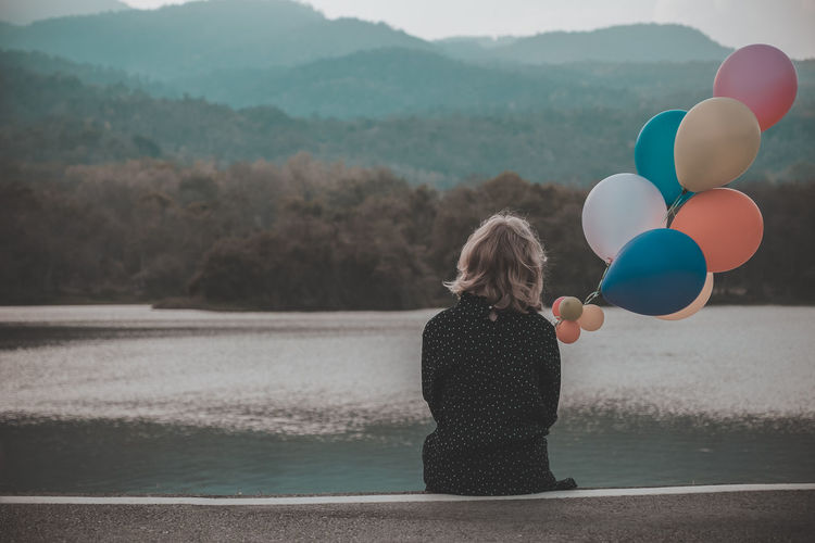 Teenager girl sitting alone in the park with balloon on mountain background. Balloon Beauty In Nature Day Females Focus On Foreground Lake Leisure Activity Lifestyles Looking At View Mountain Nature One Person Outdoors Real People Rear View Scenics - Nature Standing Tree Water Women