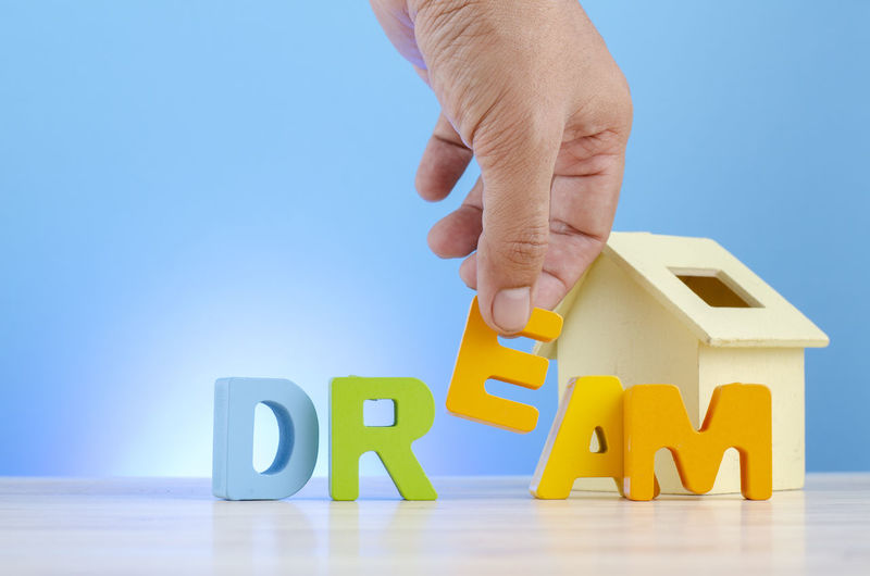 mortgage and new home concept, hand holding alphabet E to complete word DREAM. Human Hand Hand Toy Block Human Body Part Text One Person Indoors  Toy Wood - Material Real People Capital Letter Holding Blue Studio Shot Table Communication Western Script Unrecognizable Person Lifestyles Finger Blue Background