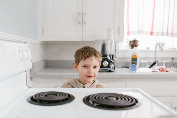 Portrait of boy standing in kitchen at home