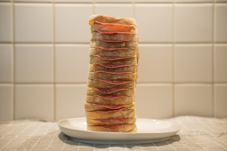 Tall Salami Sandwich Sandwich Abundance Bread Breakfast Close-up Domestic Room Focus On Foreground Food Food And Drink Freshness Indoors  Indulgence No People Plate Ready-to-eat Salami Snack Stack Still Life Table Tall Tall - High Temptation Tile Wall - Building Feature