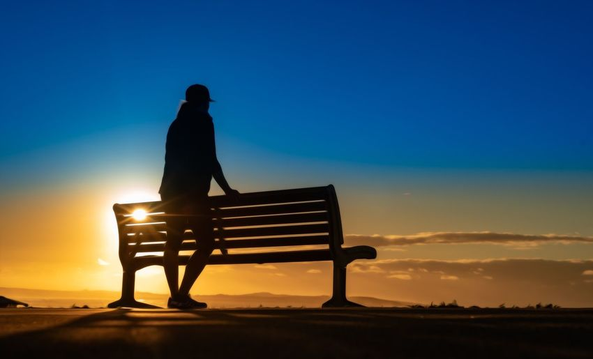 Silhouette man sitting on bench at sunset
