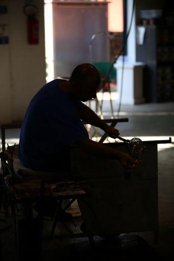 Murano Murano Murano Glass Murano Italia Murano Island Murano, Italy Concentration Craftsperson Day Glass Maker Holding Indoors  Instrument Maker Men Murano & Burano Muranoglass Music Musical Instrument Musician Occupation One Person People Preparation  Real People Sitting Skill  Workbench Working Workshop