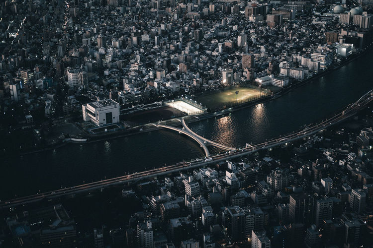 High angle view of river amidst buildings in city at night