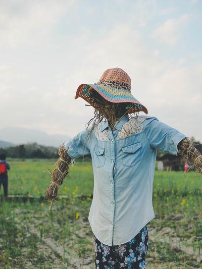 Scarecrow on farm against cloudy sky