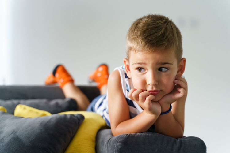 Portrait of boy sitting on sofa at home