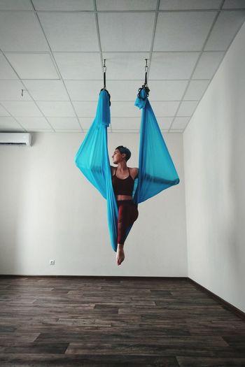 Full length of woman dancing against wall