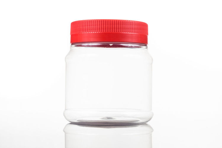 Plastic jar bottle with red cover lid against white background Blank Bottle Close-up Container Copy Space Cover Cut Out Empty Food And Drink Glass - Material Healthcare And Medicine Indoors  Lid No People Plastic Polyurethane Red Red Color Still Life Studio Shot Transparent White Background White Color